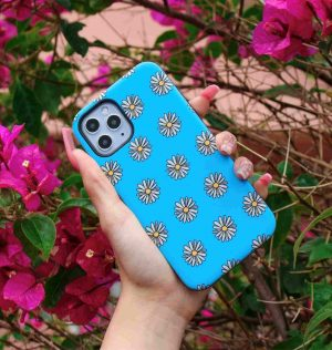Hand holding a blue phone case decorated with white and yellow daisies