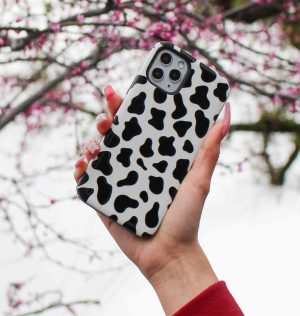 Hand holding a phone case with black and white cow design