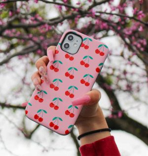 Hand holding a pink phone case decorated with red cherries