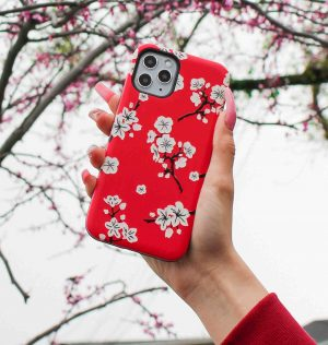 Hand holding a red phone case decorated with white blossom