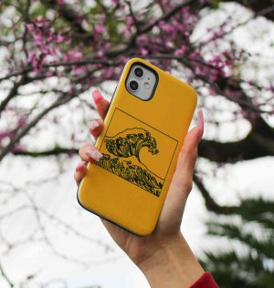 Hand holding a yellow phone case with a wave printed on the front