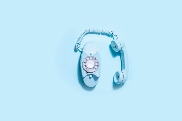 Blue vintage telephone set against a blue background