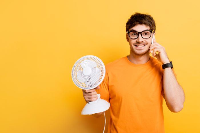 Man cooling overheated phone with fan