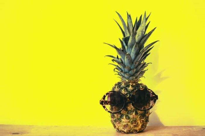 Pineapple wearing sunglasses set against a yellow background